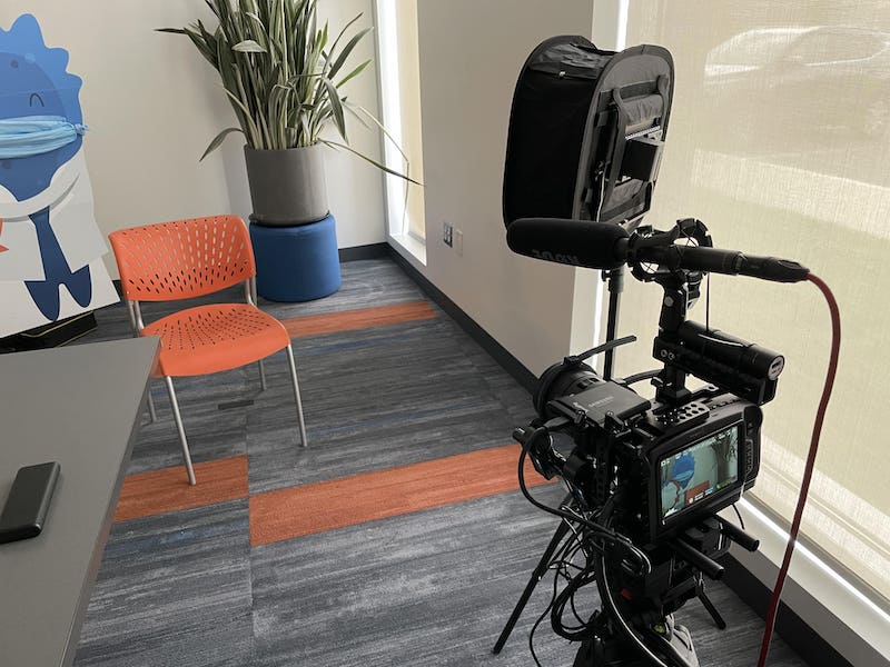 Camera set up with a chair in front of it and the Blugene mascot cutout wearing a mask in the back
