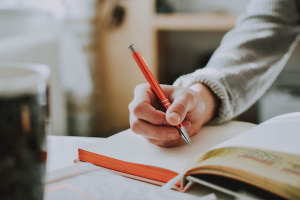 Close up image of a person writing in a notebook with an orange pen